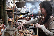 Scene of a woman in the Middle Ages working on a stall in a street market, weighing out chestnuts from a wicker basket. Image taken from the filming of 'Paris la ville a remonter le temps' written by Carlo de Boutiny and Alain Zenou, directed by Xavier Lefebvre, a Gedeon Programmes production. Picture by Manuel Cohen