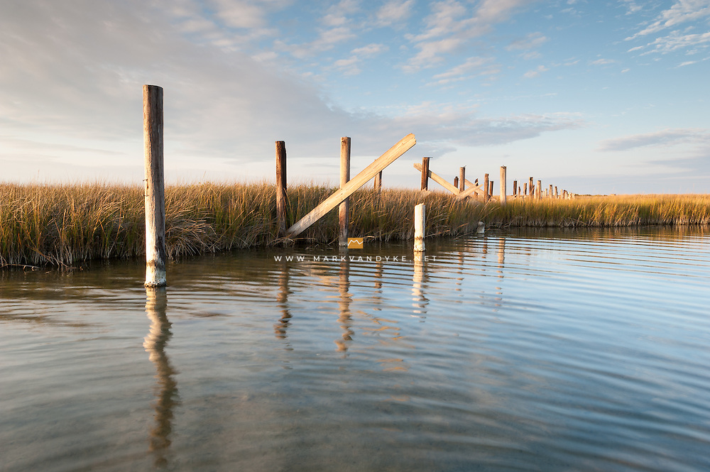 Abandoned timber pilings indicate a bridge at sometime in the past over the Pamlico Sound in the Pea Island National Wildlife Refuge.  The Outer Banks are a series of barrier islands along the coast of North Carolina.