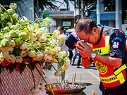 29 OCTOBER 2018 - PHRA PRADAENG, SAMUT PRAKAN, THAILAND: A city code officer prays at a shrine near the finish line of the long boat races in Phra Pradaeng. The longboat races go about one kilometer down the Chao Phraya River to the main pier in Phra Pradaeng. The boats are crewed by about 20 oarsmen. Longboat racing traditionally marks the end of the Buddhist Rains Retreat (called Buddhist Lent) in Thai riverside communities.        PHOTO BY JACK KURTZ