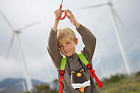 Boy (7-9) playing with umbrella at wind farm