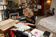 "March 6, 2015, Paris, France. Writer Maryse Wolinski (1943, Algiers) working at her desk, in the Paris' apartment where Georges and Maryse Wolinski used to live. Two month after the death of Georges Wolinski, the apartment is full of souvenirs and notes, attesting a half-century-long love relation. In 2016 Maryse Wolinski published the book ""Chérie, je vais à Charlie"" about her husband and the attack on Charlie Hebdo. The cartoonist Georges Wolinski was 80 years old when he was murdered by the French jihadists Chérif en Saïd Kouachi, he was one of the 12 victims of the massacre in the Charlie Hebdo offices on January 7, 2015 in Paris. Charlie Hebdo published caricatures of Mohammed, considered blasphemous by some Muslims. During his life, Georges Wolinski defended freedom, secularism and humour and was one of the major political cartoonists in France. The couple was married and had lived for 47 years together. Photo: Steven Wassenaar."