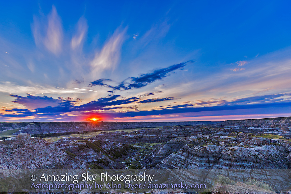Sunset on August 1, 2015 at the Horsethief Canyon Viewpoint overlooking the Red Deer River, north of Drumheller, Alberta, on the Dinosaur Trail scenic drive. The name comes from the pioneer days when horses would get lost in the Badlands here and then re-emerge found, but with a new brand on them. The region is home to rich deposits of late Cretaceous dinosaur fossils. Just south of here is the world class Royal Tyrrell Museum, a centre of research into dinosaurs and prehistoric life. <br /> <br /> This is a single-exposure frame (not HDR) from a 300-frame time-lapse sequence, with the Canon 6D and 16-35mm lens.