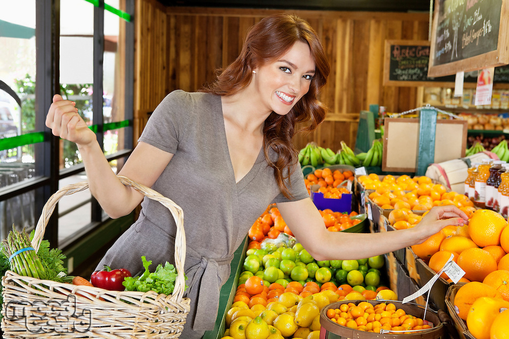 Portrait of a happy young female shopping for fruits in market