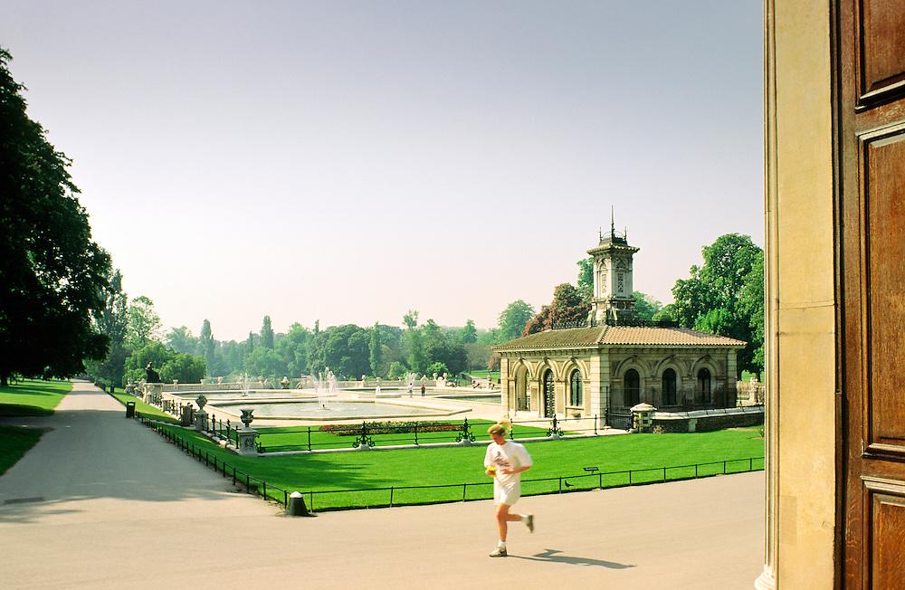 Slightly motion blurred runner jogger in the Italianate Garden corner of Kensington Gardens public park, London, UK. Summer