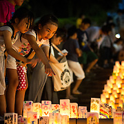 NAGASAKI, JAPAN - AUGUST 8 : Young girls look at candle-lit paper lanterns with written message at Nagasaki Peace Park on the eve ahead of the 71st anniversary activities, commemorating the atomic bombing of Nagasaki on August 8, 2016 in Nagasaki, southern Japan. On August 9, 1945, during World War II, the United States dropped the second Atomic bomb, a plutonium implosion-type bomb on Nagasaki city, killing an estimated 40,000 people which ended the World War II. (Photo by Richard Atrero de Guzman/NURPhoto)