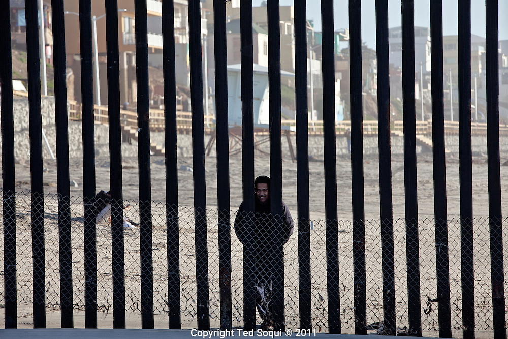 A Mexican man looks through the border fence from the Mexico side of the border fence..The rusty border fence that separates the U.S and Mexico extends briefly in to the Pacific Ocean. The once porous beach border area is now highly patrolled by U.S. Border Patrol, with very few Mexican immigrants making their passage in to the U.S..