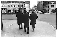 3 men with dark coats and hats, Broadway, New York City. Street photography. 1980