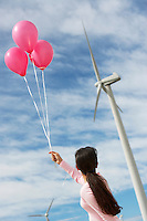 Girl (7-9) playing with balloons at wind farm