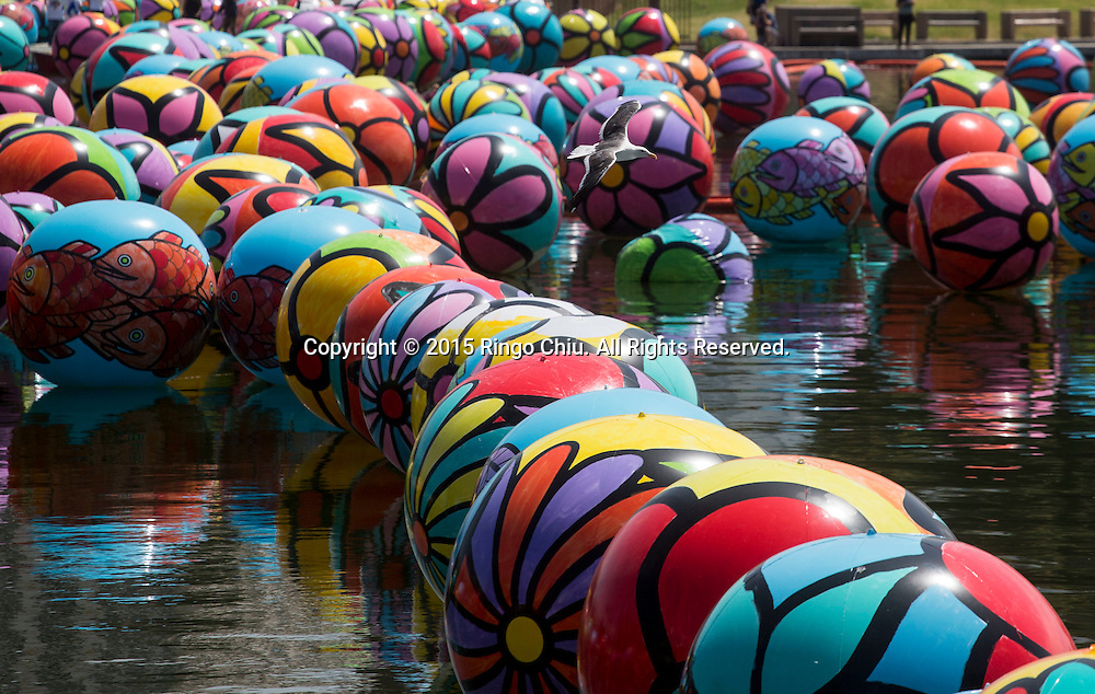 The hand-painted vinyl balls floating in the MacArthur Park Lake as part of a large-scale public arts installation organized by the Portraits of Hope charity in Los Angeles, California on August 26, 2015. The work titled ``The Spheres at MacArthur Park,'' involves filling the park's 8.39-acre lake with about 3,000 balls, each 4 to 6 feet in diameter and covered in bright floral and fish patterns. (Photo by Ringo Chiu/PHOTOFORMULA.com)