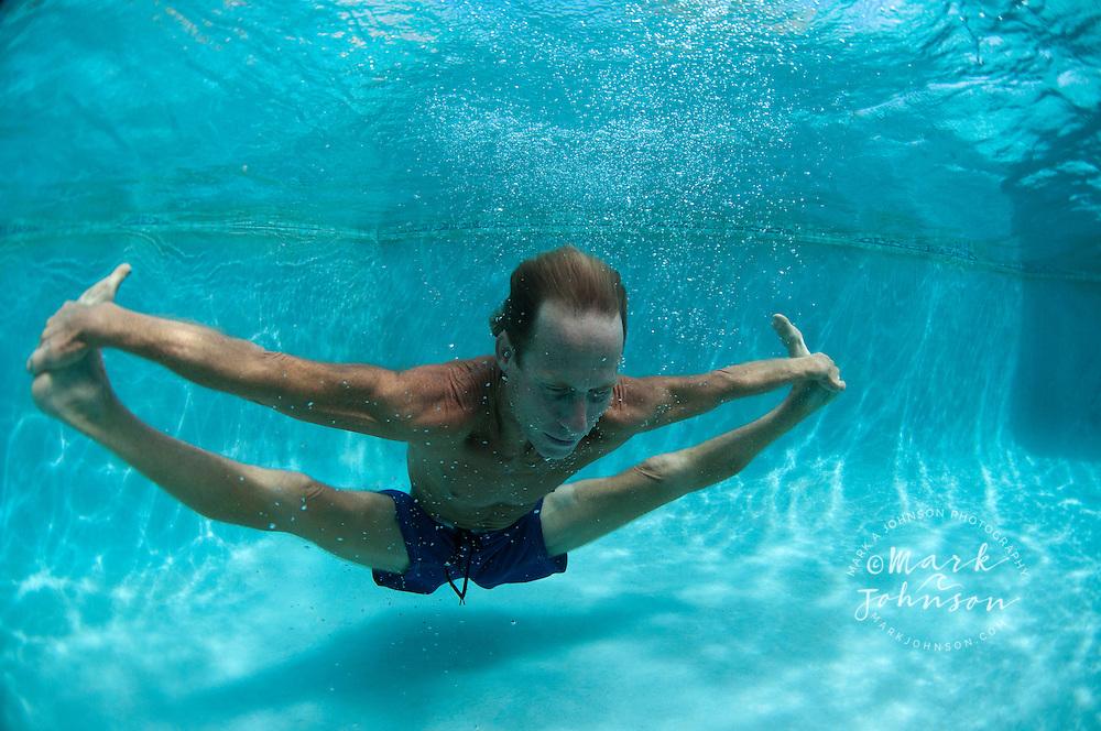 Man doing yoga underwater in pool, Kauai, Hawaii