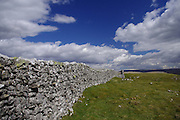 A traditional dry stone wall undulates over the hillside and into the distance above Crummackdale, North Yorkshire. The dramatic cumulonimbus cloudscape and deep blue sky in this wide angle view give the impression of being on top of the world.<br />