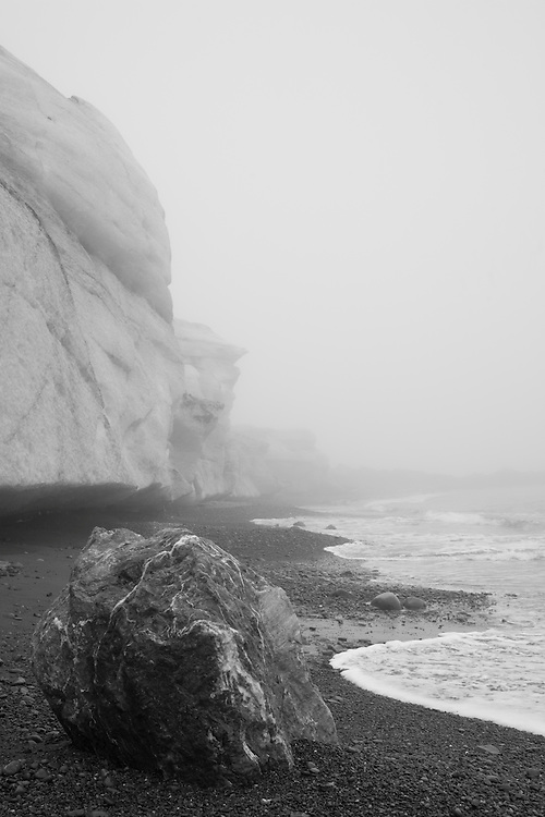 Antarctica, South Georgia Island (UK), Black and white image of large boulder left on gravel beach near glacier's terminal moraine on foggy late summer day at Trollhul harbor