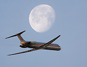 An American Airlines jet, from oakland Airport, flies near a view of the moon on Jan 6., 2007...PHOTO COPYRIGHT 2006 LANCE CHEUNG.This photograph is NOT within the public domain..This photograph is not to downloaded, stored, manipulated, printed or distributed with out the written permission from the photographer. .This photograph (on this web site) is protected under domestic and international laws.<br />
