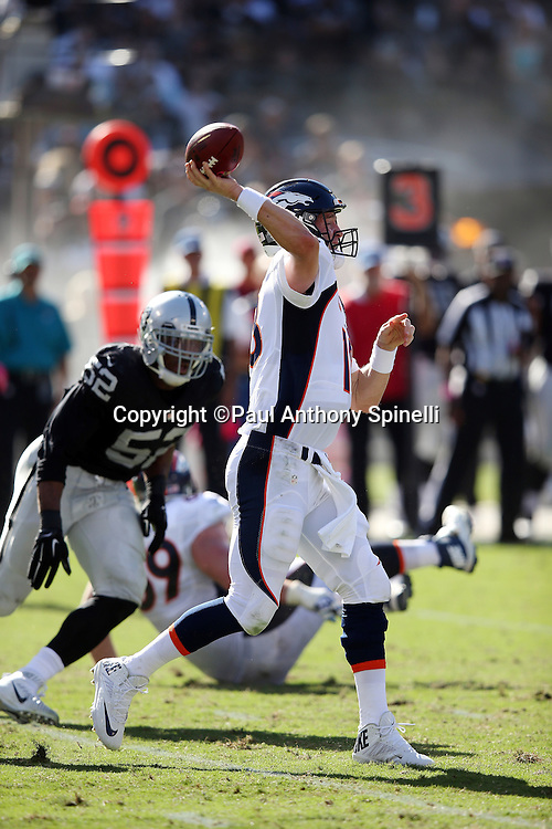 Denver Broncos quarterback Peyton Manning (18) throws a pass while pressured from behind by Oakland Raiders defensive end Khalil Mack (52) during the 2015 NFL week 5 regular season football game against the Oakland Raiders on Sunday, Oct. 11, 2015 in Oakland, Calif. The Broncos won the game 16-10. (©Paul Anthony Spinelli)