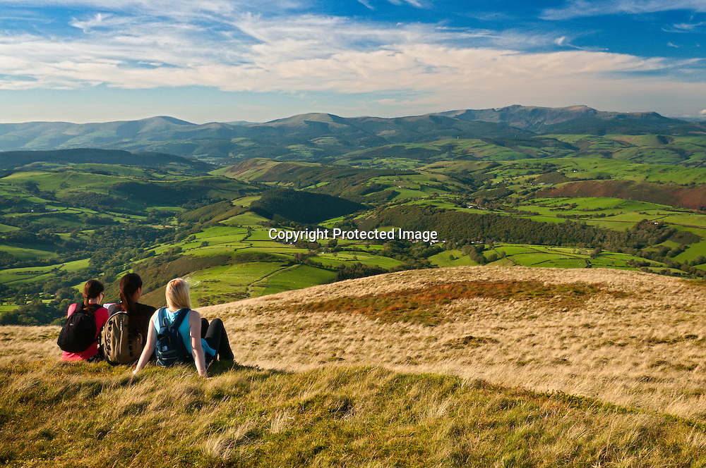 Three female walkers resting on summit of Foel Fadian, looking north to Cadair Idris<br /> Cambrian Mountains<br /> Glyndwr's Way<br /> Powys<br /> Mid<br /> Walking<br /> Activities and Sports