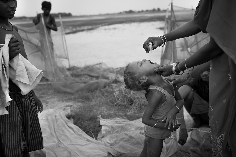 A child is given the poio vacicne at a bassa on a remote isolated house during vaccination day on the flood plains of the Kosi river near Kusheshwar Asthan (E), Bihar.