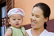 "19 FEBRUARY 2008 -- SANGKLABURI, KANCHANABURI, THAILAND:  WAWA, a Burmese refugee, and her daughter at Baan Unrak Children's Home in Sangklaburi, Thailand. Baan Unrak children's home and school, established in 1991 in Sangklaburi, Thailand, gives destitute children and mothers a home and career training for a better future. Baan Unrak, the ""Home of Joy,"" provides basic needs to well over 100 children, and  abandoned mothers. The home is funded by donations and the proceeds from the weaving and sewing shops at the home. The home is a few kilometers from the Burmese border. All of the women and children at the home are refugees from political violence and extreme poverty in Burma, most are Karen hill tribe people, the others are Mon hill tribe people. The home was started in 1991 when Didi Devamala went to Sangklaburi to start an agricultural project. An abandoned wife asked Devmala to help her take care of her child. Devmala took the child in and soon other Burmese women approached her looking for help.    Photo by Jack Kurtz"