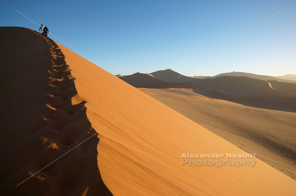 Namibia, Namib desert - Travelers hike along a dune ridge on a massive dune deep in the Namib desert near the access point of Sossusvlei