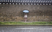 A woman stops walking to take shelter from torrential rain shower in Seoul, South Korea, June 22, 2016. Photo by Lee Jae-Won (SOUTH KOREA)  www.leejaewonpix.com