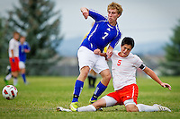 Post Falls High's Scott Benner slides in front of Adam Broshiem from Coeur d'Alene to knock the ball away during the first half of Thursday's game.
