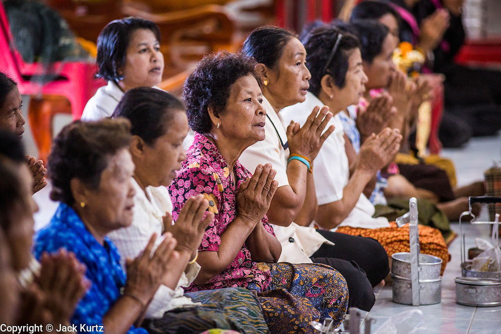 31 OCTOBER 2012 - YARANG, PATTANI, THAILAND: Members of Wat Kohwai pray before leaving the temple for a procession to Yala on Ok Phansa. Ok Phansa marks the end of the Buddhist 'Lent' and falls on the full moon of the eleventh lunar month (October). It's a day of joyful celebration and merit-making. For the members of Wat Kohwai, in Yarang District of Pattani, it was a even more special because it was the first time in eight years they've been able to celebrate Ok Phansa. The Buddhist community is surrounded by Muslim villages and it's been too dangerous to hold the boisterous celebration because of the Muslim insurgency that is very active in this area. This the year the Thai army sent a special group of soldiers to secure the village and accompany the villagers on their procession to Yala, a city  about 20 miles away.   PHOTO BY JACK KURTZ
