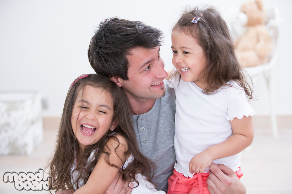 Happy father with daughters spending quality time together at home