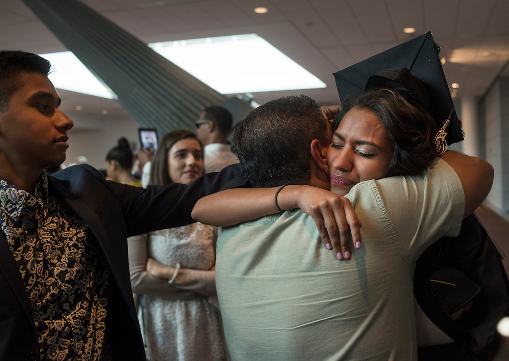Maria Duarte, a DACA recipient, embraces her father while her brother David , left, age16, watches following Chatham University's graduation at the David L. Lawrence Convention Center. Duarte is the first person in her family to graduate from college. She received a BA in psychology.