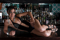 Sensual woman in swimsuit posing in a restaurant bar.