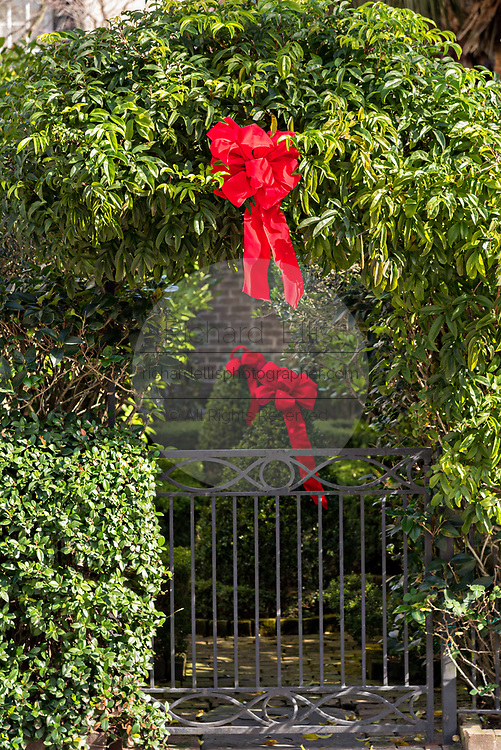 A Christmas wreath hangs from a wrought iron gate on a historic home along King Street in Charleston, SC.