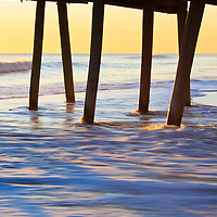 Breaking waves, shadows, and silhoutte of the fishing pier against sunrise, Virginia Beach, Virginia.