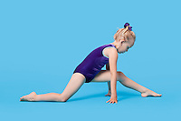 Young girl in bodysuit stretching legs over blue background