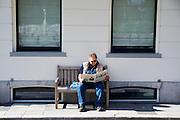 In Utrecht geniet een man op een bank van de lentezon terwijl hij de Volkskrant leest.<br /> <br /> In Utrecht a man is enoying the nice weather on a bench while reading a Dutch newspaper.