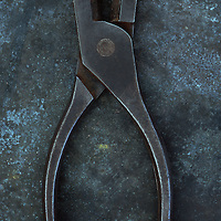 Vintage blunt-nosed pliers lying slightly open on tarnished metal sheet