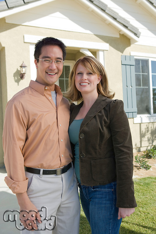 Couple in front of new house, portrait