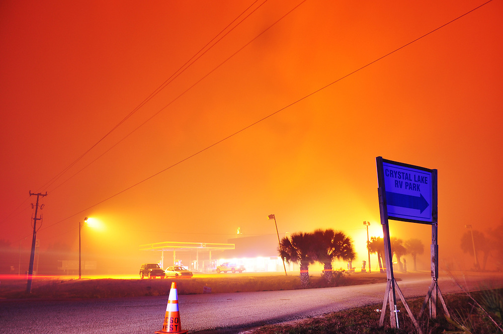 Andrew Knapp, FLORIDA TODAY -- Feb. 28, 2011 -- Smoke rises from a massive wildfire Monday evening behind the Stuckey's store and BP gas station at Stuckway Road and Interstate 95 in Mims.