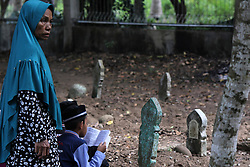 June 16, 2018 - Lhokseumawe, Indonesia - A child seen reading the Quran next to a grave with his mother during the pilgrimage..Muslims seen with their relatives' grave during a pilgrimage at the public cemetery in Lhokseumawe City. Most Muslims in Aceh already made the last grave pilgrimage before entering the holy month of Ramadan and on the day of Eid al-Fitr, to pray for the families of those who have died. (Credit Image: © Maskur Has/SOPA Images via ZUMA Wire)