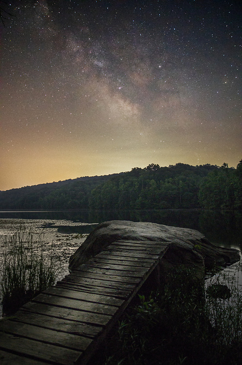The Milky Way aligns with a plank set up over a rock on the still waters of Plum Orchard Lake in Fayette County, West Virginia.