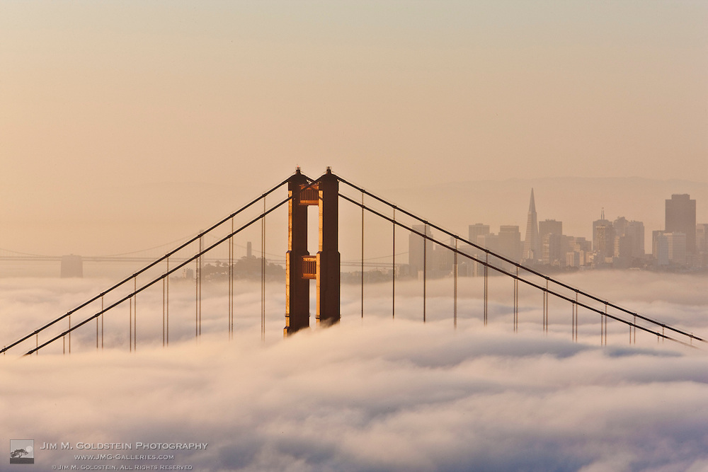 Fog shrouds the Golden Gate Bridge and the downtown San Francisco skyline at sunrise - California