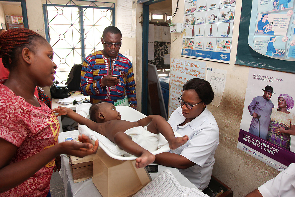 INDIVIDUAL(S) PHOTOGRAPHED: From left to right: Okobo, unknown, unknown, Lucy Offiong. LOCATION: Epko Abasi Clinic, Calabar, Cross River, Nigeria. CAPTION: Nurses carry out standard checks to evaluate a child's health, noting his weight and other measurements.