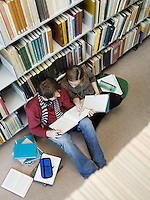 Students sitting on floor doing homework in library