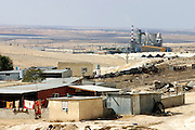 Bedouin family homes stand in unrecognised village of Wadi el Na'am, pop. 4000, close to Beer Sheva, the capital of the Negev, a large deserted area in the south of Israel. Wadi el Na'am is located near a large industrial site, Ramat Hovav, and has no infrastructure or electric energy. Water is provided only via storage tanks. It has no health services as the only clinic is deemed illegal and bound to be demolished, as the rest of the structures in the area. Numbering around 200.000 in Israel, the Bedouins constitute the native ethnic group of these areas, they farm, grow wheat, olives and live in complete self sufficiency. Many of them were in these lands long before the Israeli State was created and their traditional lifestyle is now threatened by subtle Governmental policies. The seven Bedouin towns already built are all between the 10 more impoverished towns in Israel. .