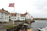 07 JUN 2003, LOSHAVN/NORWEGEN:<br /> Loshavn, ein kleines Fischerdorf mit typischen weiss gestrichenen Holzhaeusern und kleinen Holzbooten, in der Naehe von Farsund, Norwegen<br /> IMAGE: 20030607-01-007<br /> KEYWORDS: Norge, Norway, Fjord, Kueste, Küste, Wasser, Holzhaus, Holzhäuser, Flagge, Fahne
