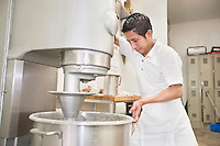 Young male baker looking into mixing bowl in bakery