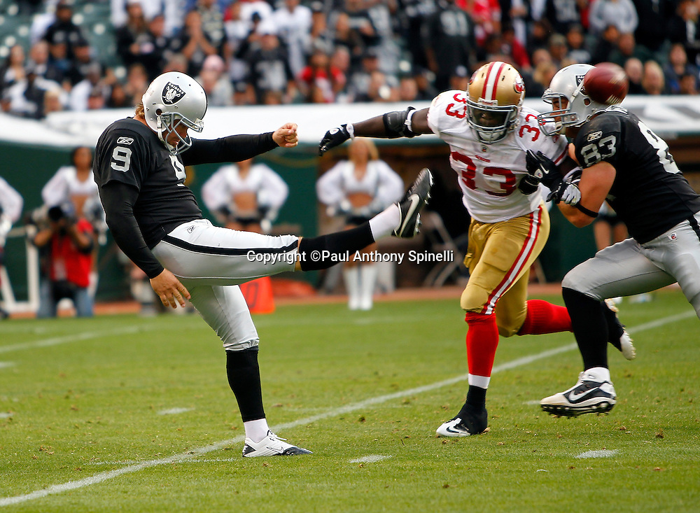 Oakland Raiders punter Shane Lechler (9) punts the ball despite pressure from San Francisco 49ers Anthony Dixon (33) who is being blocked by Raiders tight end Brandon Myers (83) during the NFL preseason week 3 football game against the San Francisco 49ers on Saturday, August 28, 2010 in Oakland, California. The 49ers won the game 28-24. (©Paul Anthony Spinelli)