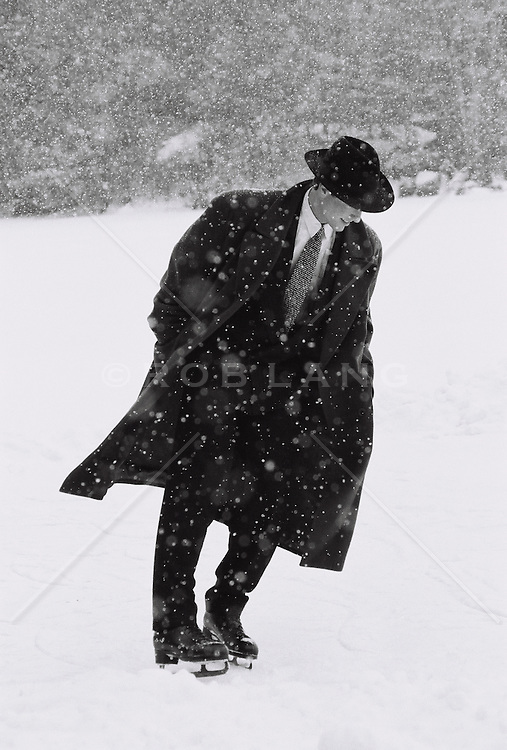Man in a suit and overcoat ice skating in a snow storm