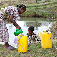 Girls carry water from a water source in Motta, Ethiopia.