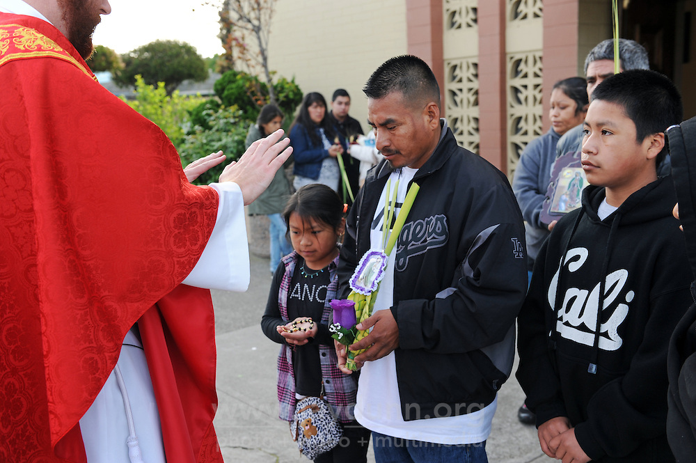 Padre Stephen Akers blesses Gabriel Lopez and his children as they exit the 7:00 AM Palm Sunday Mass at St. Mary's in Salinas.