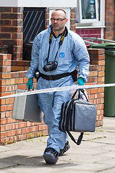 28/05/2016. London, UK. A police forensic investigator on Payne Street, Deptford, where a 16-year-old boy was stabbed 'repeatedly' shortly after midnight on Saturday 28 May 2016. The victim's condition is said to be 'critical', and a police cordon remains in place as investigations continue. Photo credit: Rob Pinney