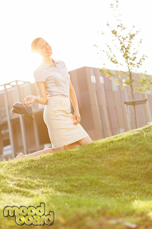 Smiling young businesswoman holding high heels while kneeling in office lawn