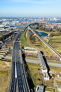 Nederland, Zuid-Holland, Rotterdam, 18-02-2015. A15 ter hoogte van knooppunt Benelux. A15 met Benneluxtunnel onder de Niuewe Maas aan de horizon, links Pernis met Shell raffinaderij.  Kolentrein op Betuweroute rijdt richting Maasvlakte en passeert leidingenviaduct.<br /> Motorway A15, connecting Port of Rotterdam with hinterland, harbours and container terminals.<br /> luchtfoto (toeslag op standard tarieven);<br /> aerial photo (additional fee required);<br /> copyright foto/photo Siebe Swart